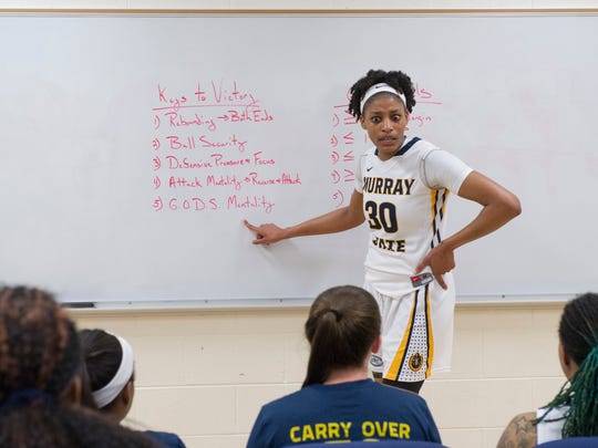"Kyra Gulledge, a 6'2"" senior for the Racers, takes to the white board to joke with her teammates before Coach Rob Cross gives his pre-game pep talk Saturday evening."