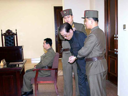 Jang Song-thaek is escorted in court on December 12, 2013.  North Korea has executed him, the uncle of its leader Kim Jong Un, after a shock purge, state news agency KCNA announced early on Dec. 13, branding the once-powerful man a