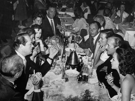 Some members of the Holmby Hills Rat Pack, a group of exceedingly well heeled Bohemians that include screen stars and millionaires from Hollywood's super-ritzy Holmby Hill section, are seen sitting at a table having cocktails at the Copa Room in Hollywood, Oct. 15, 1956..  Shown left to right are Humphrey Bogart; producer Sid Luft; Lauren Bacall; Judy Garland; Ellie Graham; agent Jack Entratter; restaurateur Mike Romanoff (partly hidden); Frank Sinatra; Mrs. Romanoff; actor David Niven; and Mrs. Niven.