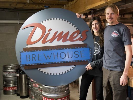Chad and Michelle Rogers, owners of Dimes Brewhouse in downtown Dimondale, hold metal signage their friend Cal Peters gave to them as a gift.  The brewhouse is slated to open Dec. 21, 2017.