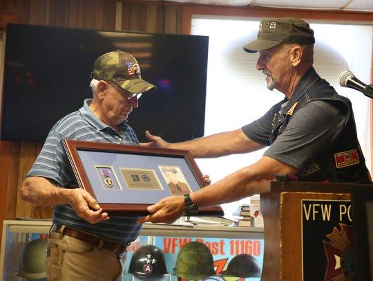 From left, David Phillip Kisor receives the returned