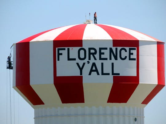In 2012 workers on a suspended scaffold apply a fresh coat of paint to the 130-foot-tall,  million-gallon landmark Florence Y'All water tower.