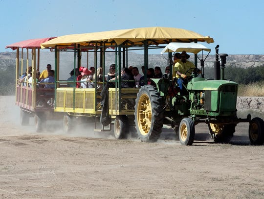 A tractor pulls visitors from the pumpkin patch Sunday