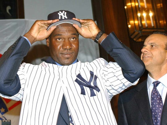 New York Yankees manager Joe Torre watches as Cuban defector and New York Yankees pitcher Jose Contreras dons a New York Yankees cap and jersey Thursday, Feb. 6, 2003, at Yankee Stadium in New York, after agreeing to a four-year $32 million