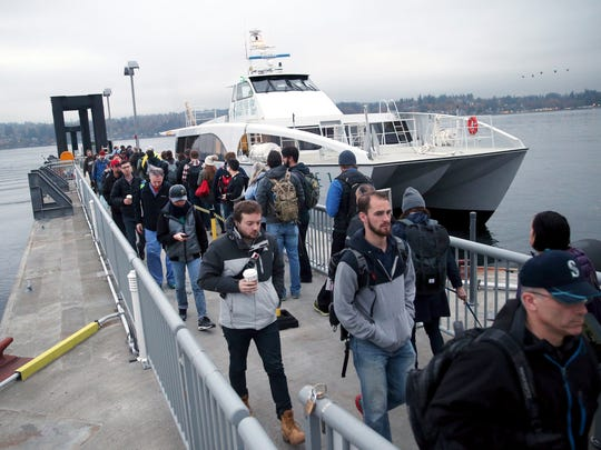 Commuters from Seattle exit the Kitsap Transit fast ferry Rich Passage 1, while Bremerton passengers get ready to board the 8 a.m. sailing to Seattle on a gray Wednesday morning.