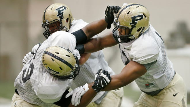 Gelen Robinson, right, during spring football practice Thursday, March 31, 2016, inside the Mollenkopf Athletic Center at Purdue University.