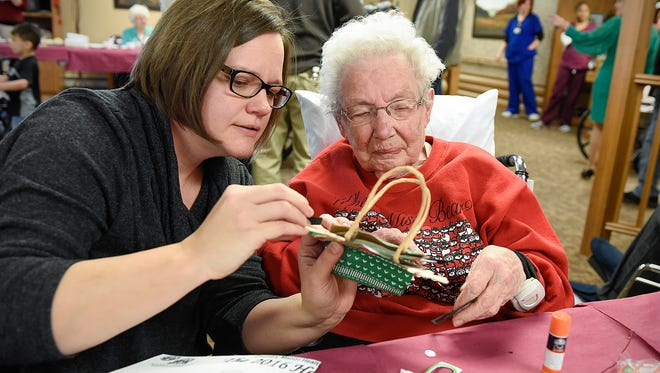Sara Neibergall, Blaine, and her grandmother Betty Vanselow make a holiday gift bag during the Hometown Christmas celebration Saturday, Dec. 10, at Country Manor Health Care & Rehab Center in Sartell.
