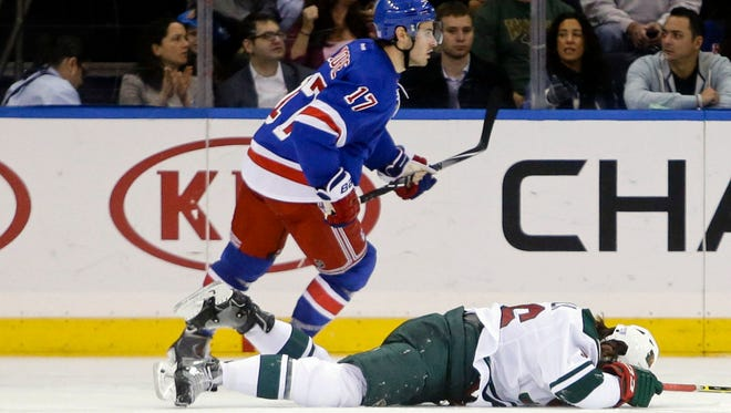Minnesota Wild's Erik Haula holds his head after being hit by the New York Rangers' John Moore (17) during the second period Monday, Oct. 27, 2014, in New York. Moore was given a match penalty for the hit.