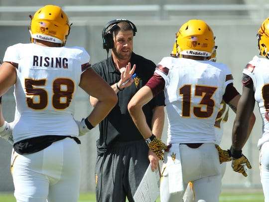 ASU offensive coordinator Billy Napier talks with his