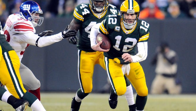 Green Bay Packers quarterback Aaron Rodgers runs upfield in the first quarter against the New York Giants during the NFC divisional playoff game at Lambeau Field in Green Bay on Sunday, Jan. 15, 2012.