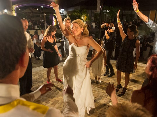 Shelly Osterhout, center, dances at her wedding reception