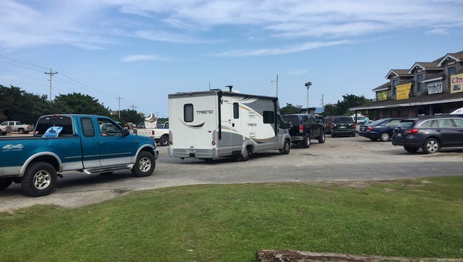 Vehicles line up at the a gas station on Ocracoke Island on North Carolina's Outer Banks, as visitors leave the island and residents fuel up.
