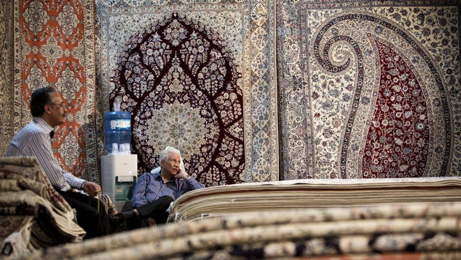 Iranian carpet businessmen sit in their stall at Iran's International hand-woven carpet exhibition in Tehran Sept. 29, 2013.