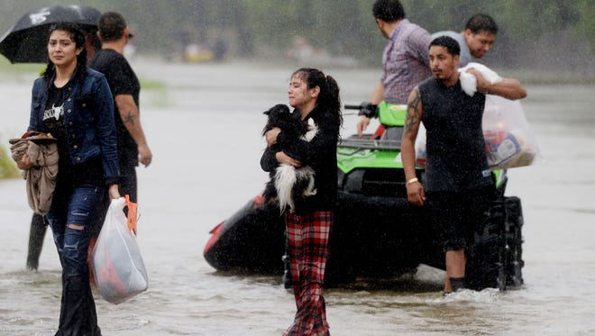 Rescue efforts are made in a subdivision off Highway 90 in the Northeast corner of the Houston area Monday morning, August 28, 2017.