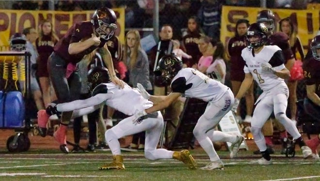 Simi Valley quarterback Cole Hauptman gets stopped by Oak Park's defense during Friday night's game.