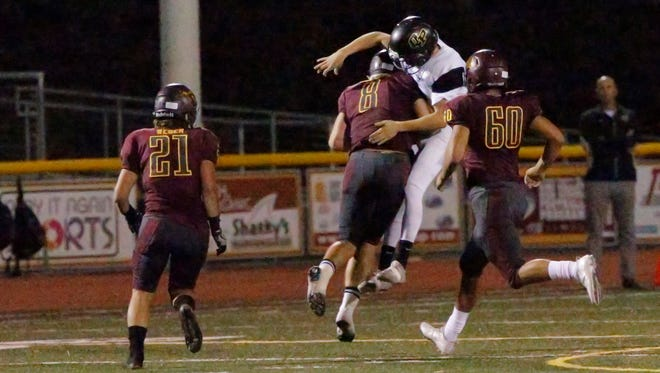 Oak Park High Vincenzo Granatelli is hit hard by Simi Valley's Juan Puentes during Friday night's Canyon League opener.