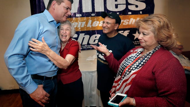 El Paso County Sheriff Richard Wiles gets a hug from supporter Blanca Torres on Tuesday night as he talks with Ray Mancera and Perla Bermudez. Wiles defeated his opponent, Republican Tom Buchino.