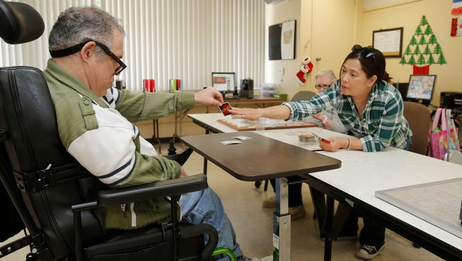 This program for disabilities will not need to leave the Thousand Oaks site it has called home for the last 27 years. The United Cerebral Palsy adult day program will get to keep its lease in the Waverly Heights neighborhood, officials decided Tuesday. Here, in a photo taken last month, staff member Jude Vinson (right) plays a game of Uno with Donald Geagan.