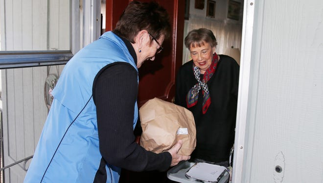 In this file photo, Maureen Dobbins, of Thousand Oaks, delivers a meal to Mary Ann Dolan, one of the local seniors who participates in the Senior Concerns Meals on Wheels program.