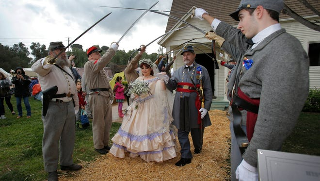 Matthew Mooradian, right, and the other Civil War re-enactors hold their swords high as Matthew's mother, Karina Mooradian, and Kevin Dunbar leave the historic St. Lima Catholic Church in Strathearn Historical Park after being wed during  Civil War Days on Saturday. Dunbar and Mooradian are also re-enactors.