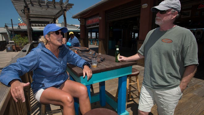 Pensacola Beach residents Connie and Rob Hoffman enjoy a cocktail at Bamboo Willie's Beachside Bar on April 7, 2017. Escambia County commissioners are split on whether an ordinance banning alcoholic beverages in public areas of Pensacola Beach has been beneficial and whether the ban should be extended.