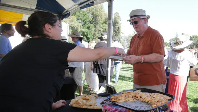 Carisa Ramos, from Valley Bakery in Oak Park, hands Tom Henderson some of the bakery's popular Quesito which is a special cheese roll, at the 2014 event.