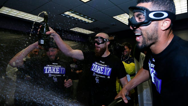 Colorado Rockies catcher Jonathan Lucroy (21) and left fielder Ian Desmond (20) celebrate after securing a National League wild card berth following a game against the Los Angeles Dodgers at Coors Field.