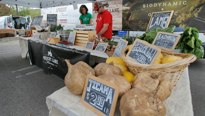 Apricot Lane Farm's Olivia Hayano and Joey Schaeffer staff their booth during the Thousand Oaks Certified Farmers' Market in this file photo.
