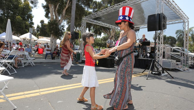 Yvonne Soto, of Port Hueneme,  and her daughter Selena dance to the sounds of the band Love Handles during the Fourth of July street fair Ventura on Wednesday.