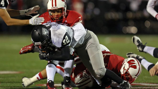 Lakota West's JaMier Jackson tackles Lakota East RB Conolly Boughner in the game between the Lakota East Thunderhawks and the Lakota West Firebirds at Lakota West High School on Oct. 31.