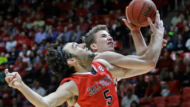 Ball State's Rocco Belcaster (5) fouls Utah's Jakob Poeltl, rear, as Poeltl goes to the basket in Friday's Utah win.