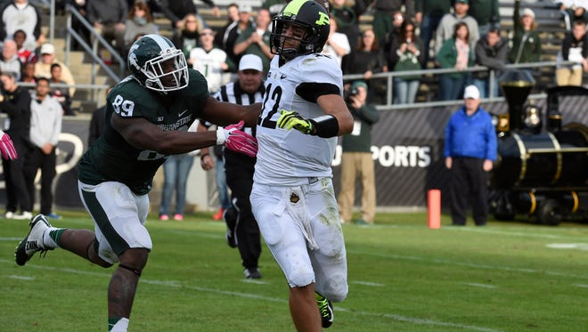 Oct 11, 2014; West Lafayette, IN, USA; Purdue Boilermakers quarterback Austin Appleby (12) runs while looking to pass and being chased by Michigan State Spartans defensive end Shilique Calhoun (89) at Ross Ade Stadium. Mandatory Credit: Sandra Dukes-USA TODAY Sports