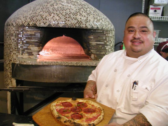 Angel Davilla presents another pizza from the flame-fed