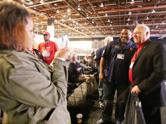 UAW  President Dennis Williams, right,  poses for a photo with Anthony Walker of Kansas City, Kan., Local Union 31,  as Dedire Hawkins, 49, left, of Kansas City, Kan., Local 31, takes their photo during day two of the 2015 Special Bargaining Convention at Cobo Center in downtown Detroit Wednesday, March 25, 2015.
