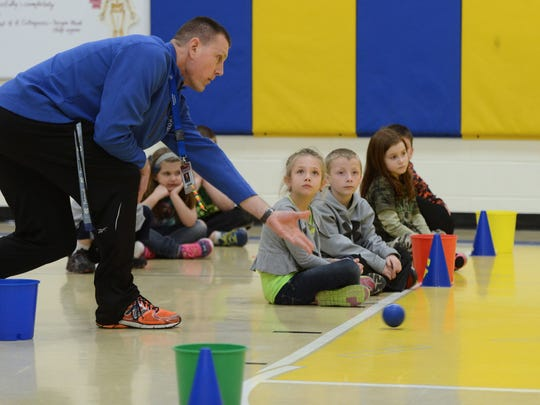Golden Apple recipient Chris Wendorf demonstrates an activity focusing on rolling, throwing and catching skills to one of his physical education classes at Sunnyside Elementary in Pulaski.
