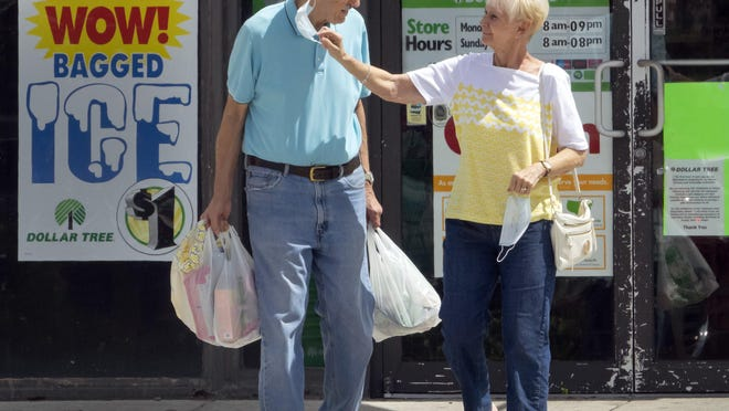 A woman takes the mask off her companion Wednesday after they leave  the Dollar Tree on Okeechobee Boulevard in West Palm Beach. Masks are now required in public places in Palm Beach County.