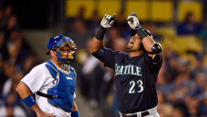 Seattle Mariners' Nelson Cruz, right, points to the sky after hitting a solo home as Los Angeles Dodgers catcher A.J. Ellis watches during the fourth inning of a baseball game, Monday, April 13, 2015, in Los Angeles.