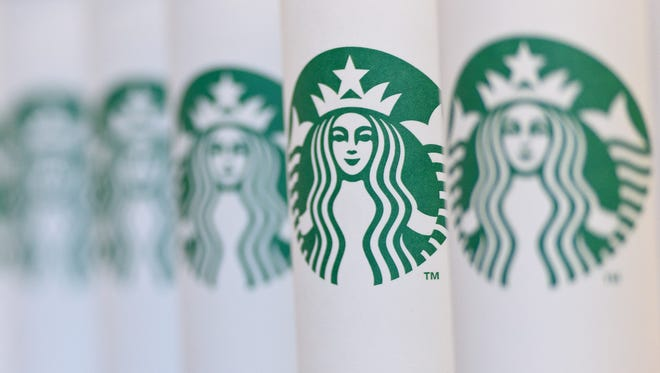 A collection of venti sized Starbucks take away cups.