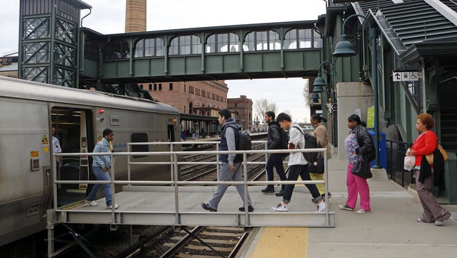 Commuters walk over a metal bridge to reach the platform and board the train at Glenwood station, May 2, 2014 in Yonkers. Glenwood is one of four Metro-North Hudson Line stations using these bridges due to a mudslide that covered tracks in Yonkers.