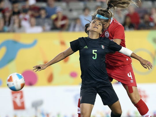 Shelina Zadorsky (in red) vies for a ball with a Mexican player in the bronze medal match of the 2015 Pan Am Games.