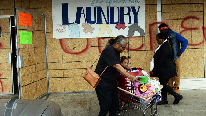 People walk past a laundry with covered windows in Ferguson, Mo., on Nov. 22, 2014.