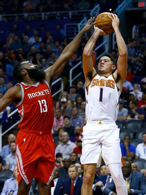 Phoenix Suns guard Devin Booker (1) tries to shoot over Houston Rockets guard James Harden (13) during the second half of an NBA basketball game Thursday, Nov. 16, 2017, in Phoenix. The Rockets won 142-116.