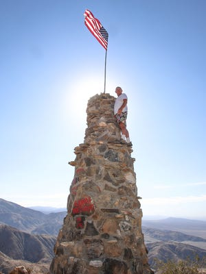 Din Kossova, of Sky Valley, stands atop the monument he unknowingly built just inside Joshua Tree National Park. Kossova was fined $9,000, and the monument will be destroyed.