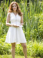 "Andrea Rooney Finn poses in a Vince Camuto sleeveless zipper dress and Vince Camuto white pumps, vintage white wrist-length gloves and silver necklace with pearl and disc that says ""dream,"" at Chadds Peak Farm in Chadds Ford, Pa. on Tuesday."