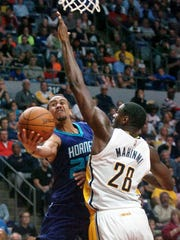 Charlotte Hornets' Brian Roberts, left, shoots around Indiana Pacers' Ian Mahinmi (28) during an NBA preseason basketball game, Thursday, Oct. 22, 2015 in Fort Wayne, Ind.