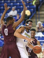 Delaware's Skye Johnson works under the basket against the College of Charleston's Donovan Gilmore (left) and Cameron Johnson in the first half at the Bob Carpenter Center Thursday.