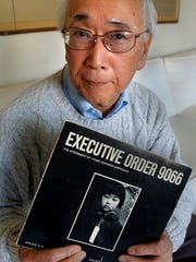 "Gordon Yoshikawa holds a book of photographs commerating the internment of Japanese-Americans in camps during World War II. The book title, ""Executive Order 9066,"" refers to the executive order by President Franklin Roosevelt to establish camps."