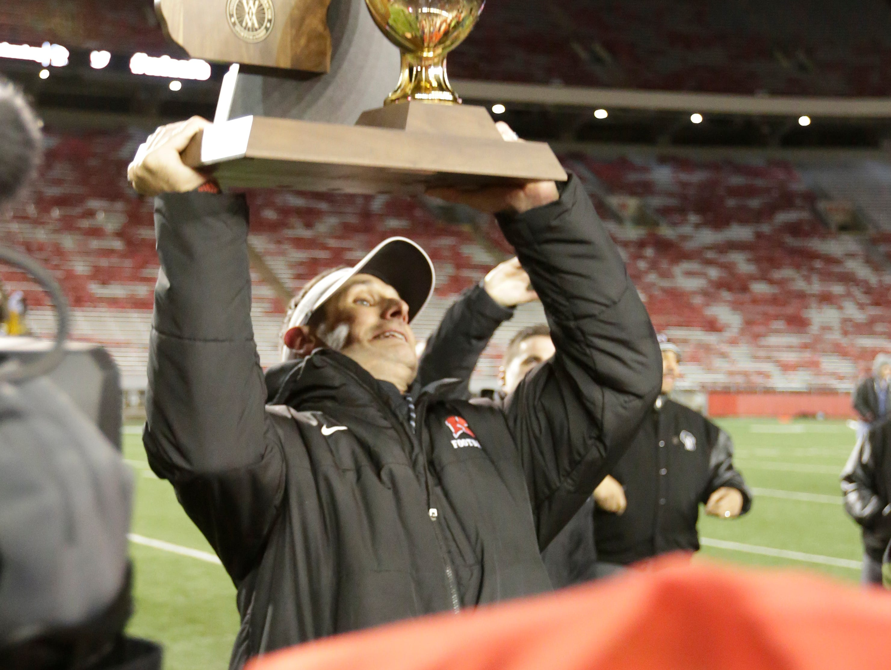 Kimberly High SchoolÕs Steve Jones hoists the Championship trophy as the Papermakers won their 4th straight championship 29 - 14. Kimberly Papermakers played Franklin Sabers in the Division 1 WIAA State Football finals held at Camp Randall in Madison, Wisc. Friday, November 18, 2016.