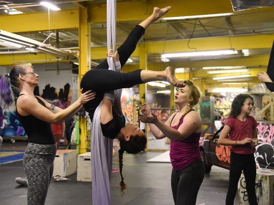 Heather Dozier, left, helps Elena Sacchi through her moves as instructor Anneliese LaTempa coaches her during a Level 2 Aerial Silks class at Urban Evolution Baltimore gym.