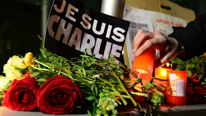 """A man lights a candle next to a poster reading """"Je suis Charlie"""" (I am Charlie) in front of the French embassy on January 7, 2015 in Berlin to express solidarity with employees of the French satirical weekly Charlie Hebdo that has been target of  an attack by unknown gunmen. German Chancellor Angela Merkel condemned the """"despicable"""" attack on Charlie Hebdo that left at least 12 people dead in a condolence letter to President Francois Hollande.       AFP PHOTO / JOHN MACDOUGALLJOHN MACDOUGALL/AFP/Getty Images ORG XMIT: 1338 ORIG FILE ID: 536538075"""